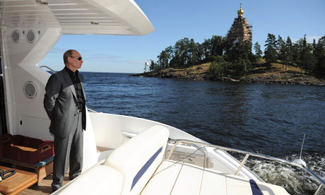 Vladimir Putin surveys the scene from the back of a boat in Karelia, north-west Russia. A new report says the Russian president has overseen a phenomenal expansion in the awarding of presidential perks. Photograph: RIA Novosti/Reuters