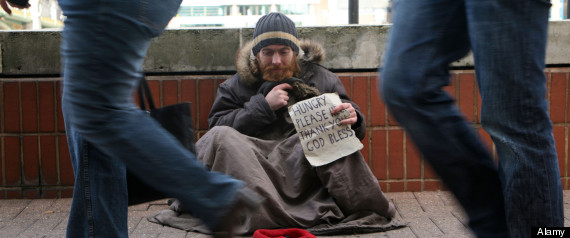 People passing a homeless man begging for money, London.