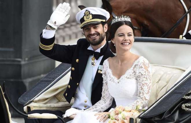 Sweden's Prince Carl Philip sits with his bride, Sofia Hellqvist in a carriage, after their wedding ceremony, in Stockholm, Sweden.